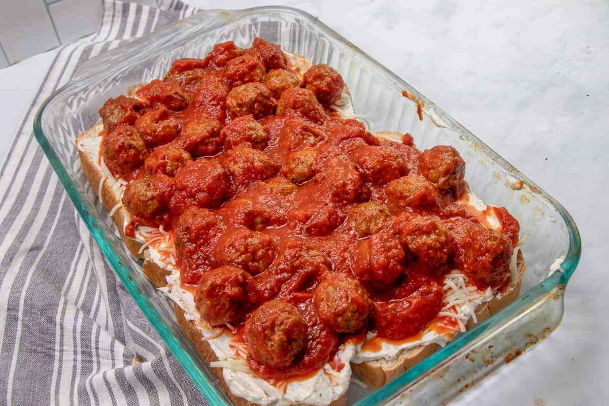 marinara sauce and meatballs layered into a glass casserole dish.