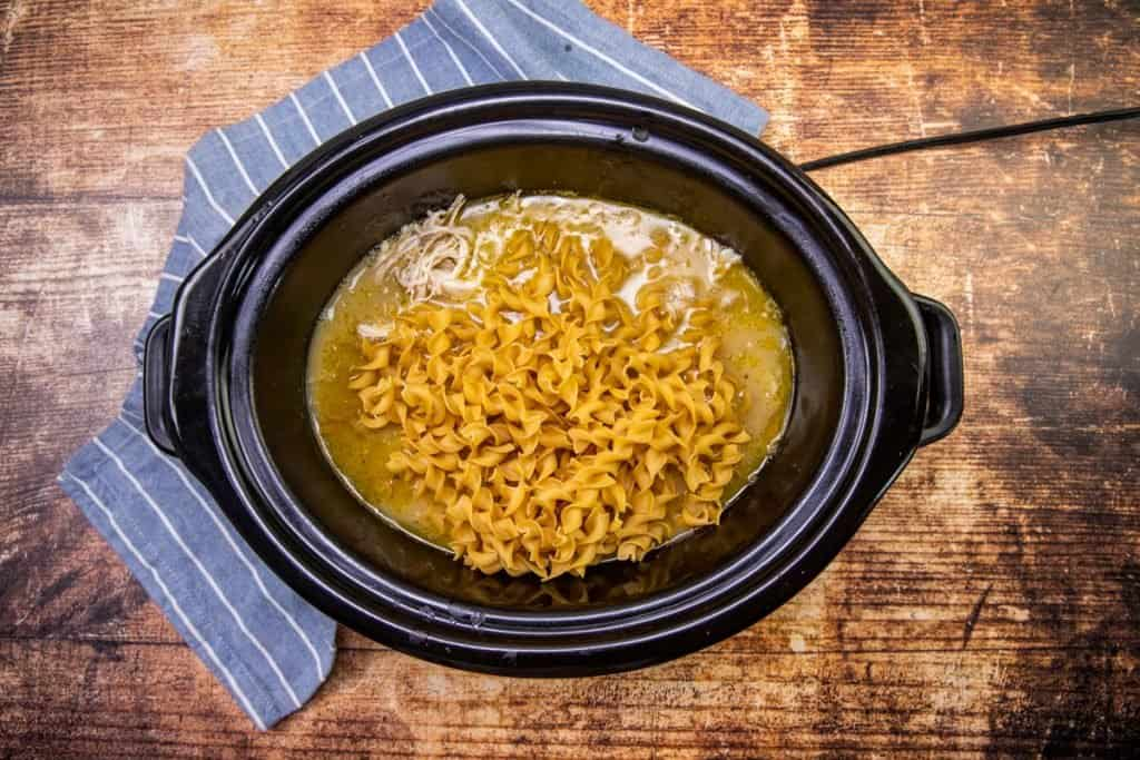 egg noodles added to the slow cooker after chicken has been cooked and shredded