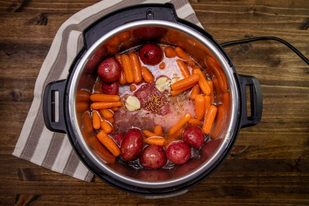 seasoned carrots and potatoes placed around brisket in 6-quart Instant Pot