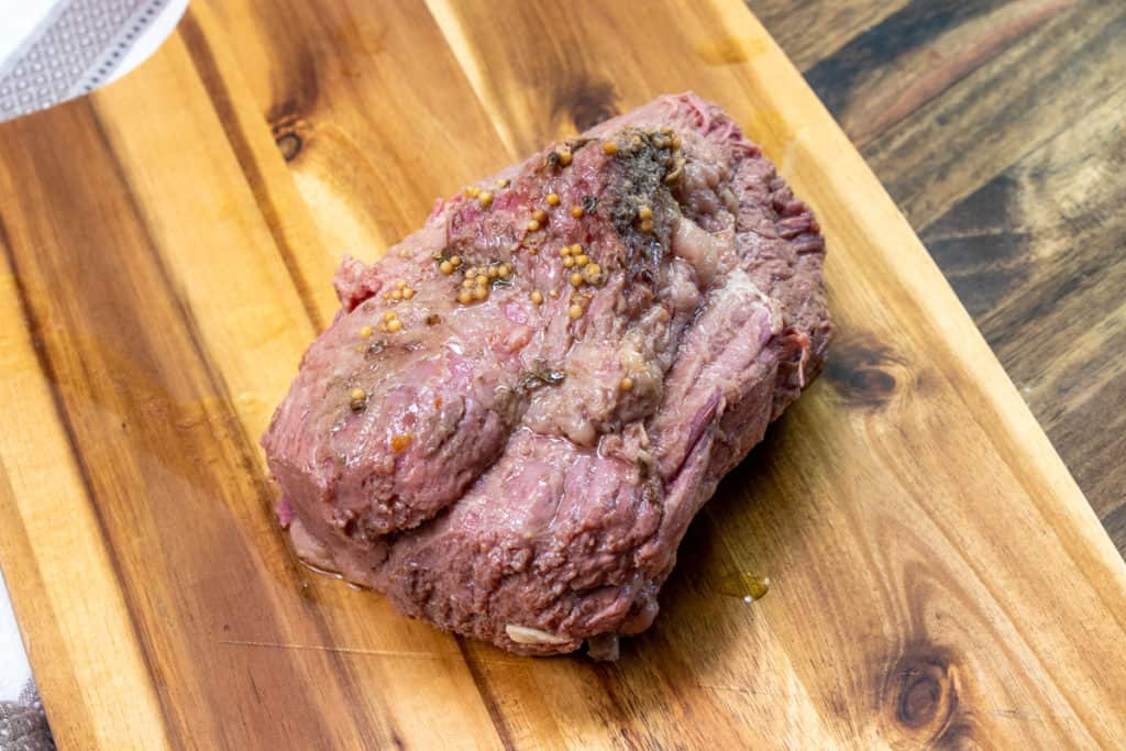 fully cooked corned beef resting on a cutting board