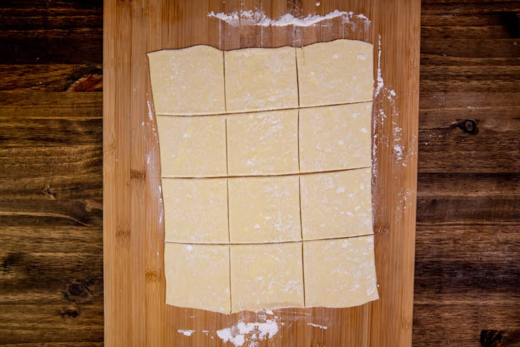 puff pastry cut into 12 squares on a cutting board