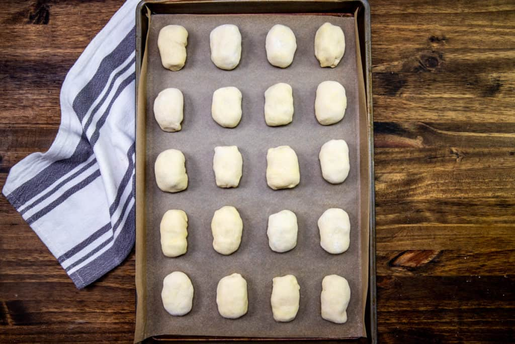 sausage rolls wrapped in puff pastry on a baking sheet lined with parchment paper