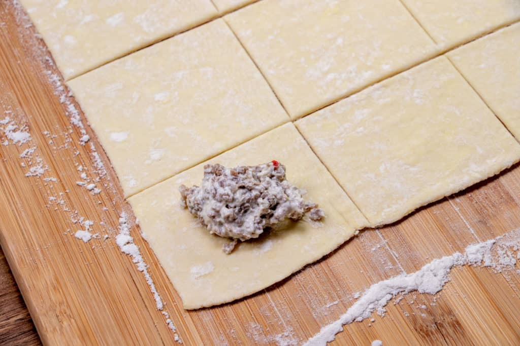 a dollop of cream cheese sausage mixture on top of puff pastry square