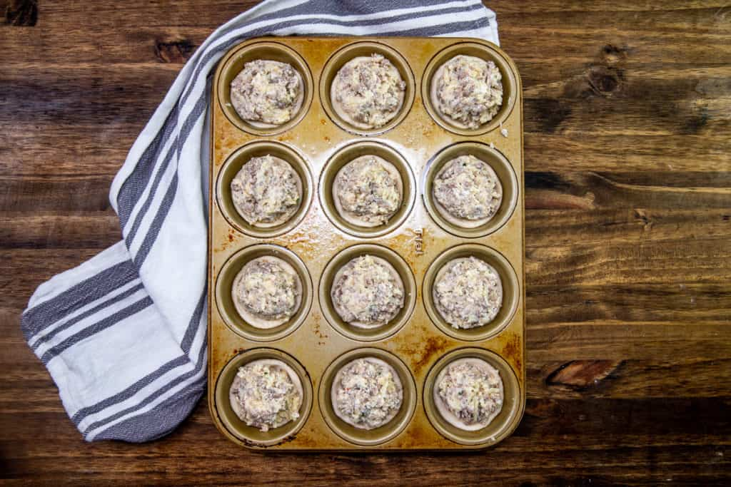 cream cheese sausage mixture added to the tops of each refrigerated biscuit in a muffin tin