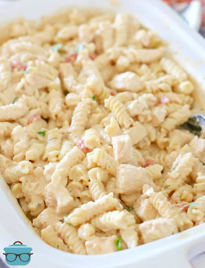 fully cooked and combined Slow Cooker Chicken Ranch Pasta recipe shown in casserole slow cooker with a serving spoon.