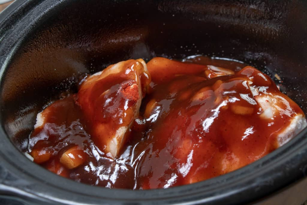 barbecue sauce poured over frozen chicken in an oval slow cooker