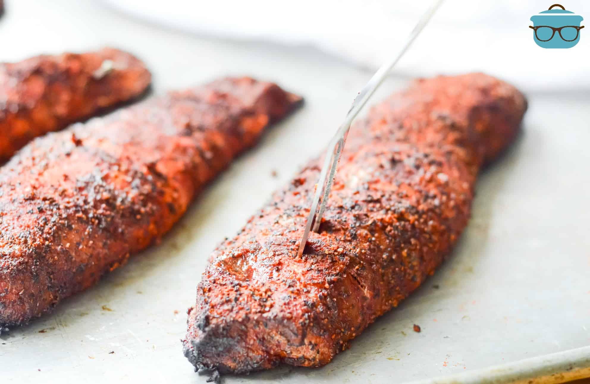 fully cooked smoked pork tenderloins on a metal baking sheet.
