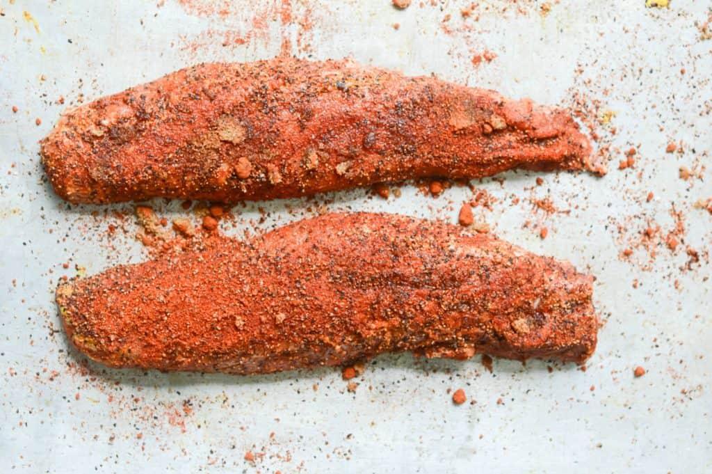 below mustard and seasoning spread onto two pork tenderloins