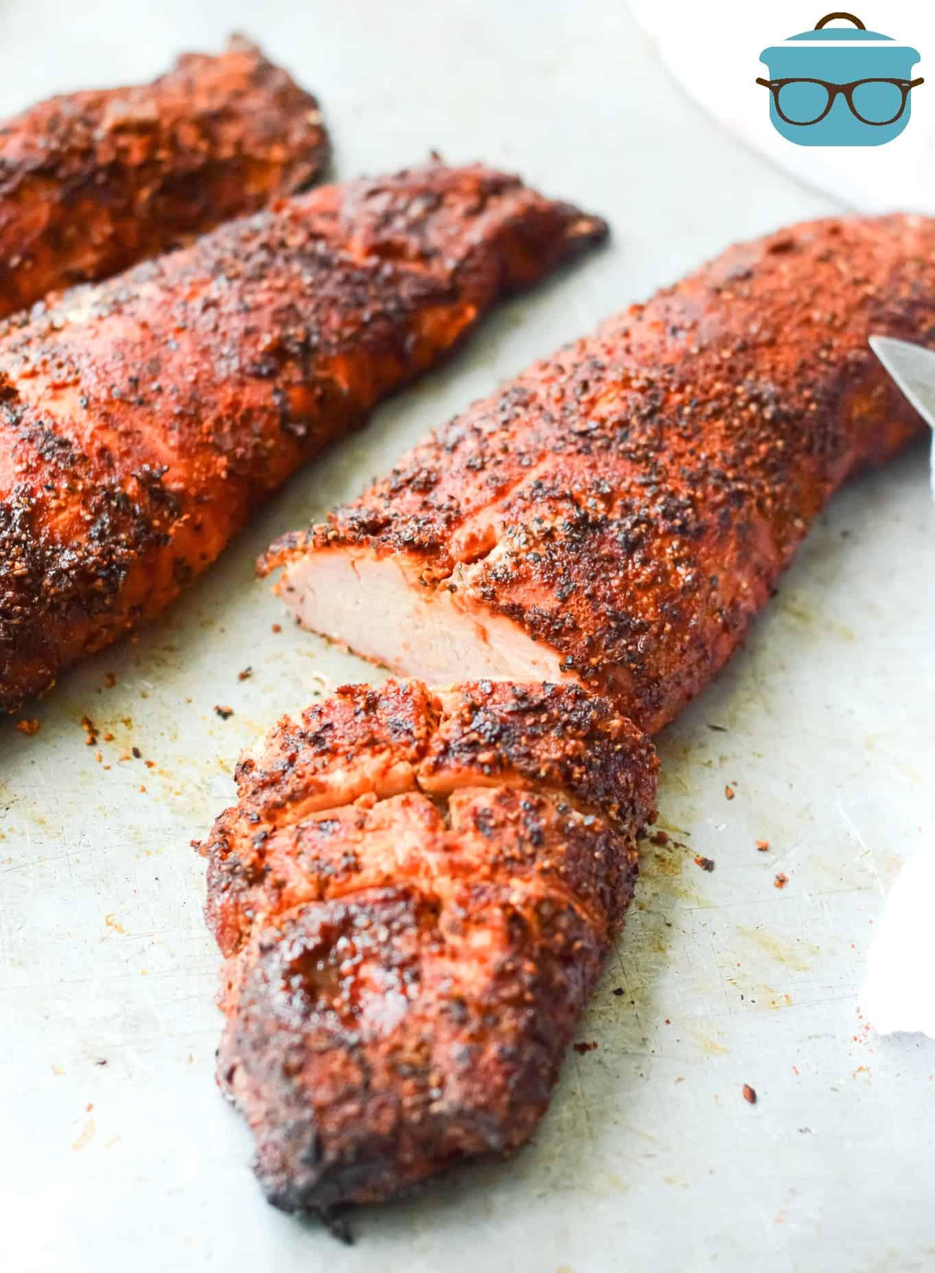 smoked pork tenderloin sliced on a baking tray.