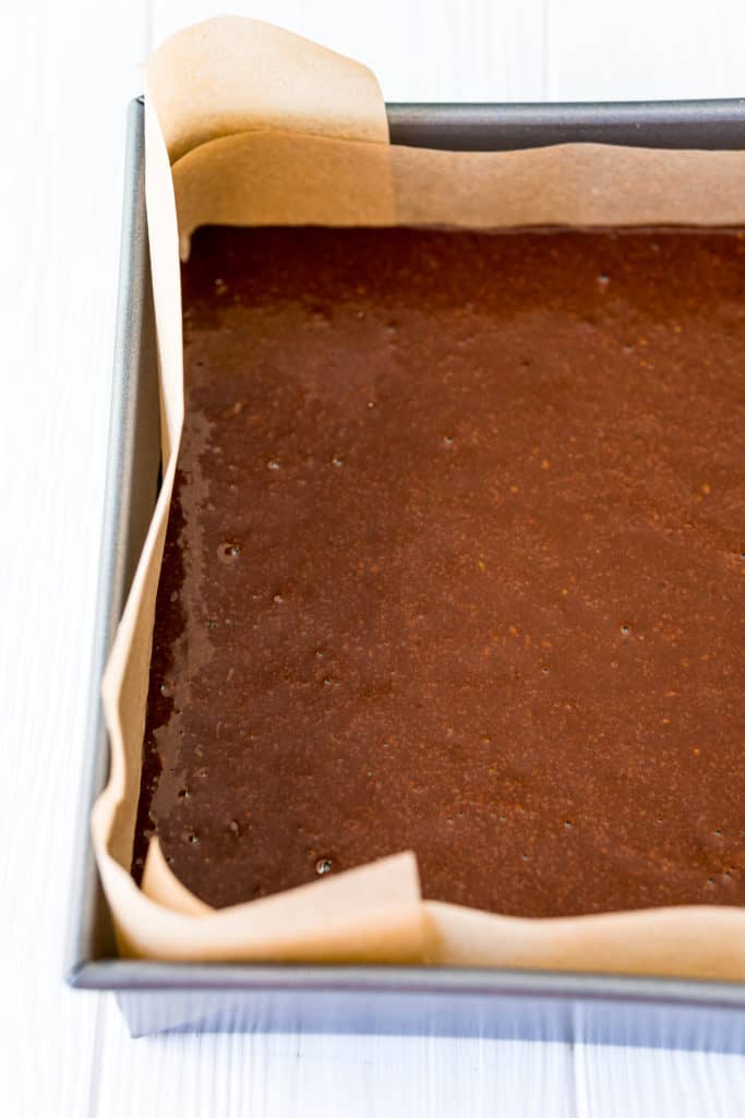 zucchini brownie batter poured into prepared baking dish with parchment paper