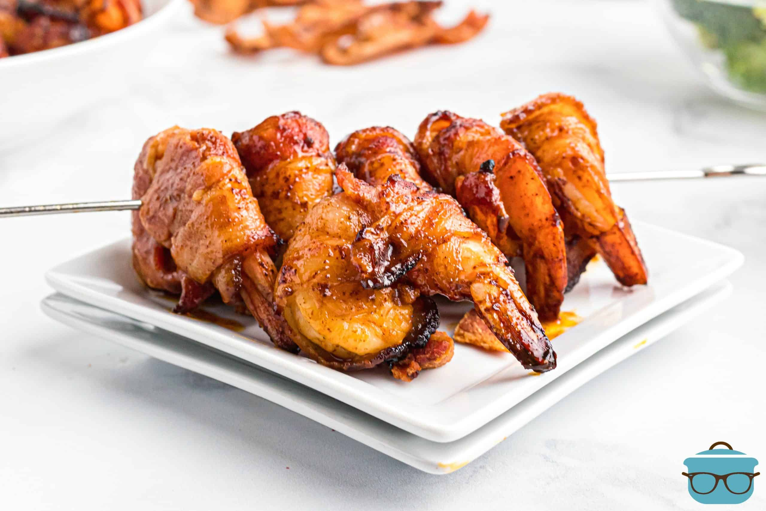 BBQ Bacon Wrapped Shrimp on a metal skewer on white plates.