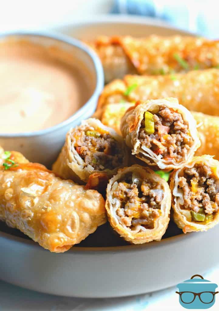 Cheeseburger Egg Rolls, fully cooked on a platter with dipping sauce in the background