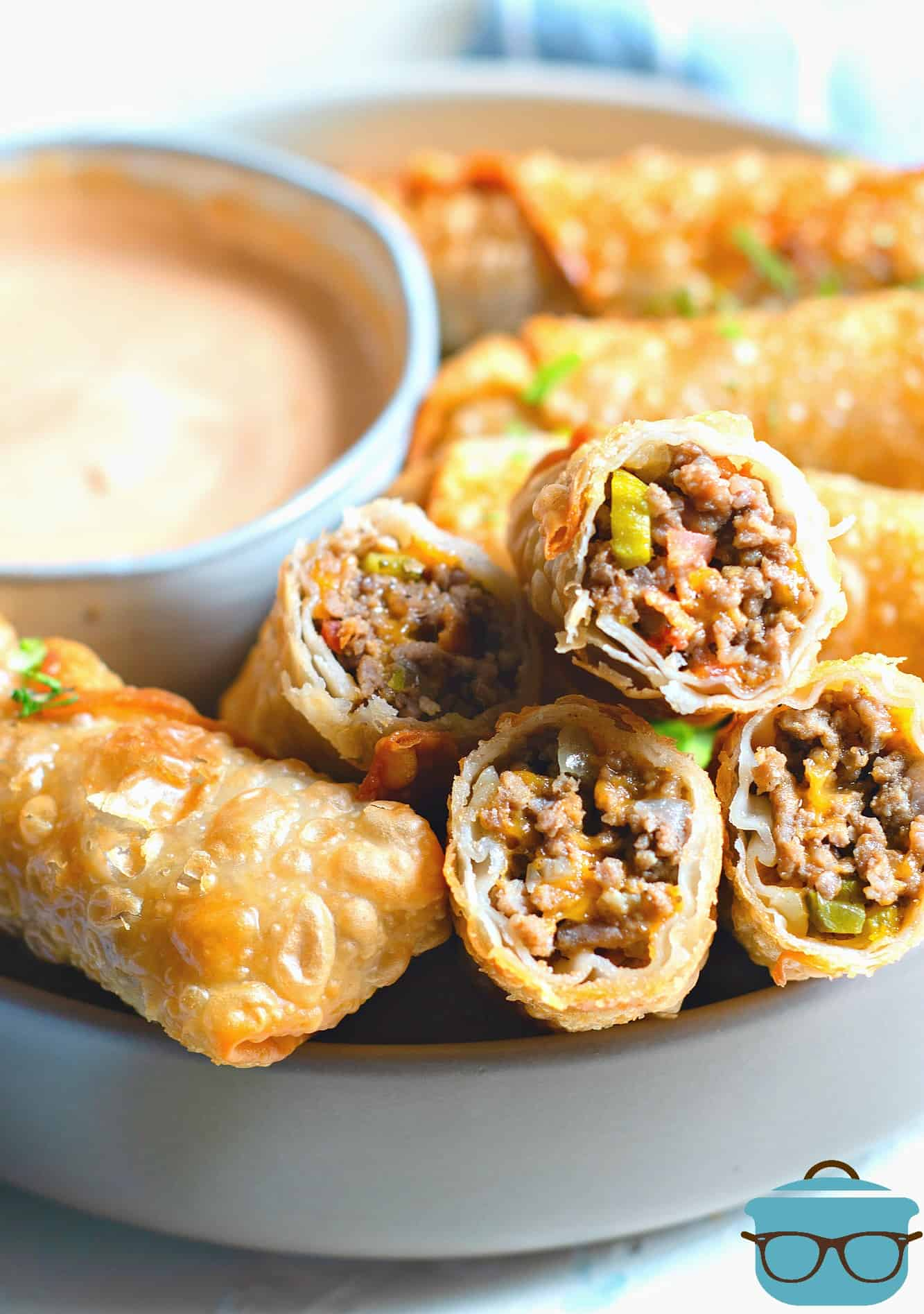 Cheeseburger Egg Rolls, fully cooked on a platter with dipping sauce in the background.