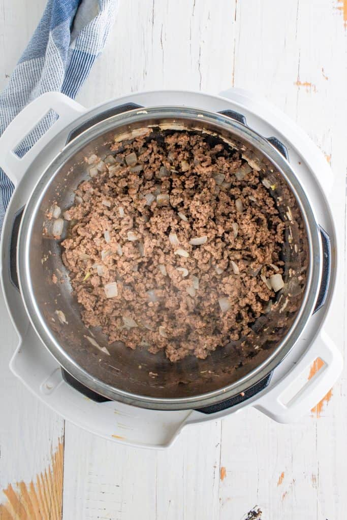fully cooked and crumbled ground beef and cooked onion in the bottom of an instant pot