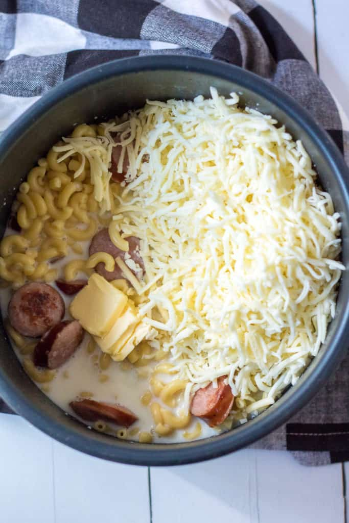 butter, evaporated milk and shredded cheddar cheese added to the macaroni and sausage
