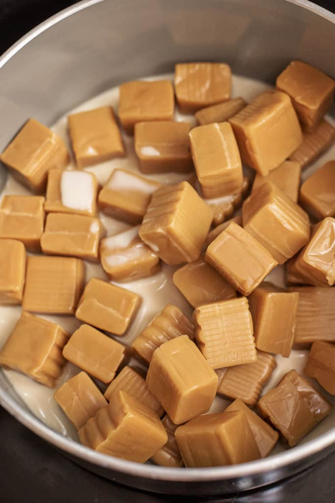 evaporated milk and caramels in the bottom of a saucepan