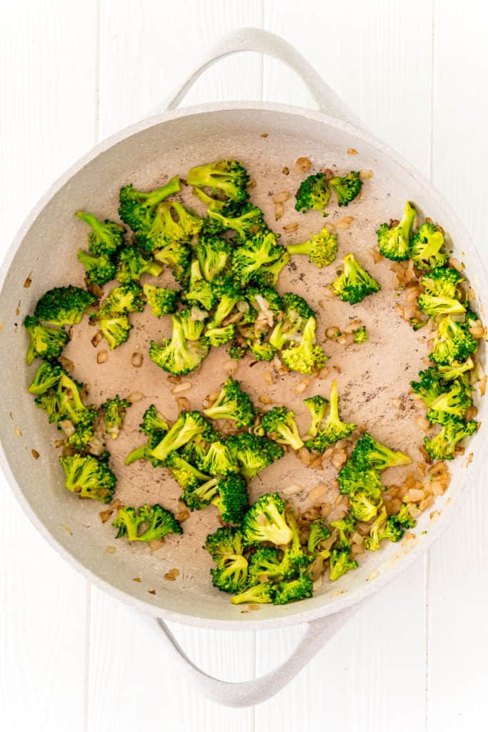 broccoli florets added to onions and oil in saute pan