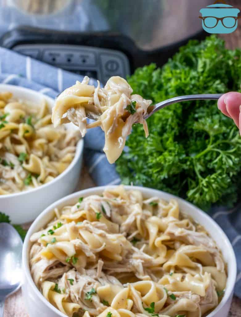 chicken and noodles shown in two white bowls and a fork scooping out some noodles from one of the bowls