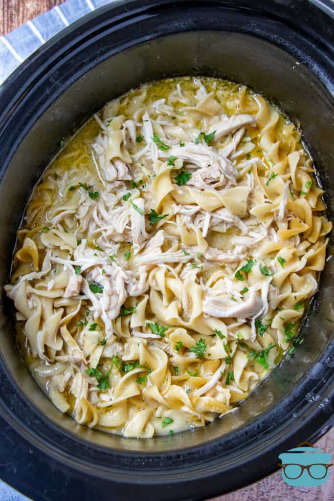 Fully cooked chicken and noodles in an oval black crock pot and topped with chopped parsley