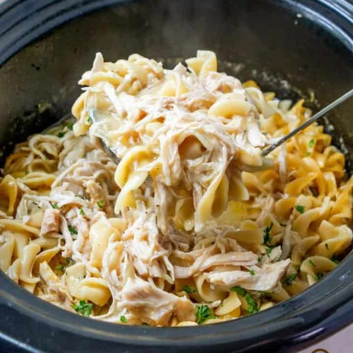 chicken and noodles scooped out of the slow cooker with a ladle