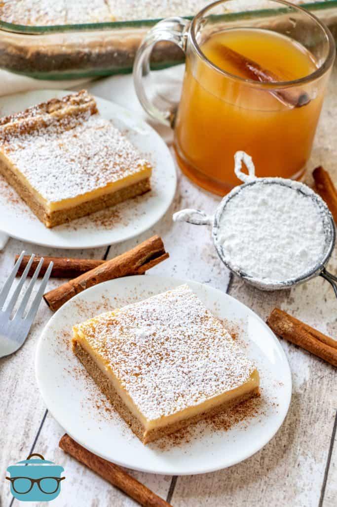 Tranches de gâteau aux épices au beurre gluant sur des assiettes blanches avec des bâtons de cannelle et un verre de cidre de pomme en arrière-plan