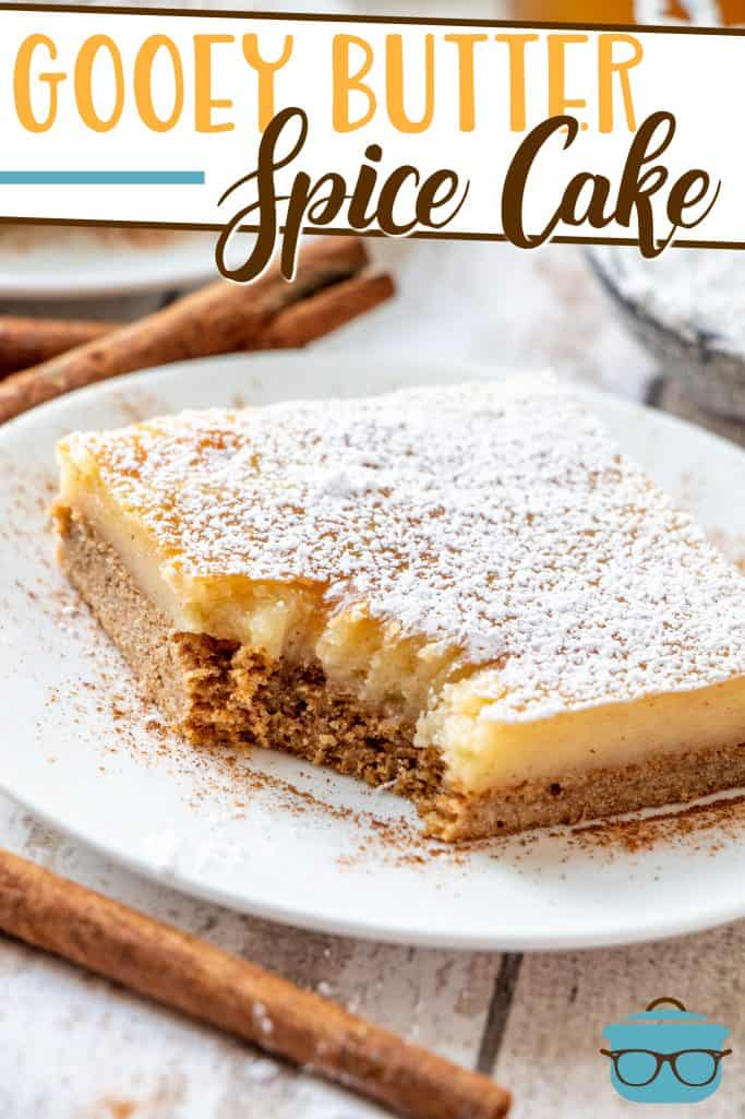 Gooey Butter Spice Cake Recette de The Country Cook, tranche illustrée sur une plaque de cercle blanc avec des bâtons de cannelle en arrière-plan