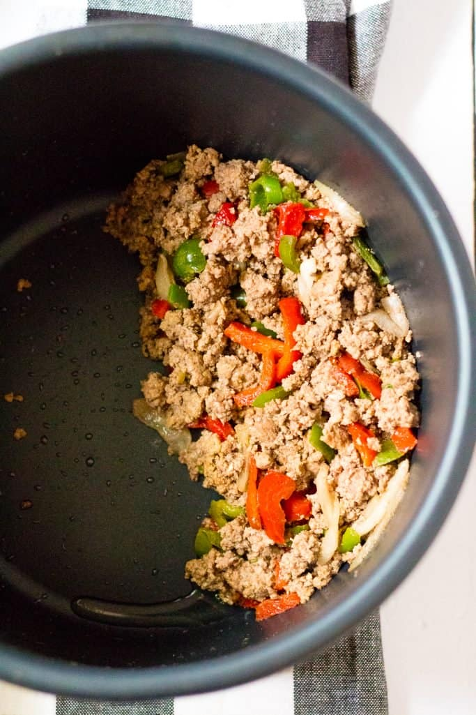 fully cooked ground beef, peppers and onions in the bottom of an instant pot insert