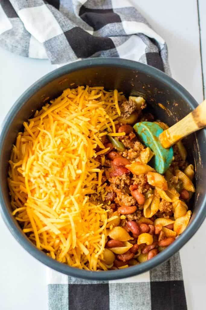 shredded cheddar cheese added to fully cooked taco pasta in the instant pot pressure cooker insert bowl