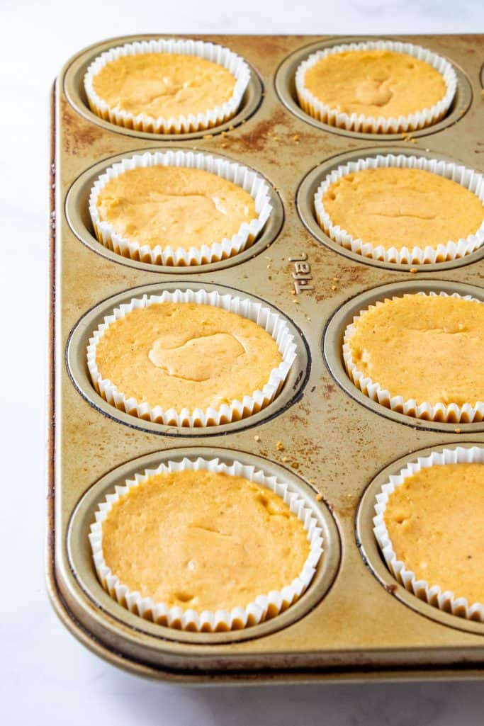 fully baked mini pumpkin cheesecakes in a muffin pan