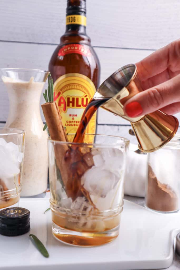pouring Kahlua into a glass with ice