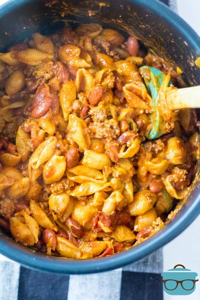 fully cooked, Cheesy Taco Pasta shown in the Instant Pot insert and a spatula