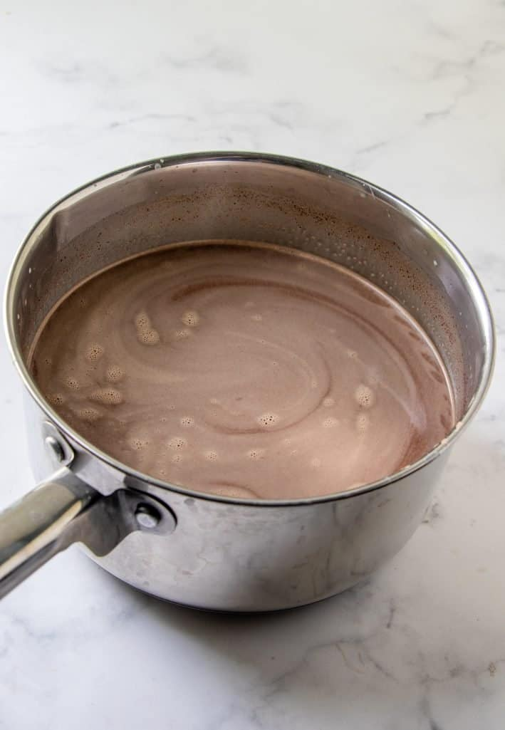 melting chocolate along with milk and sweetened condensed milk in a silver sauce pot