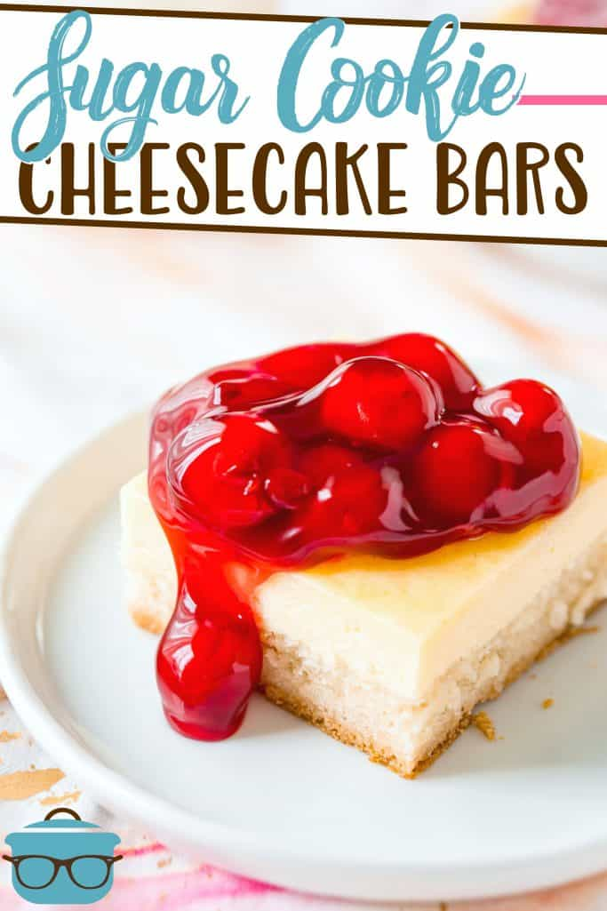 Sugar Cookie Cheesecake Bars recipe from The Country Cook, slice shown on a round white plate and cheesecake is topped with cherry pie filling