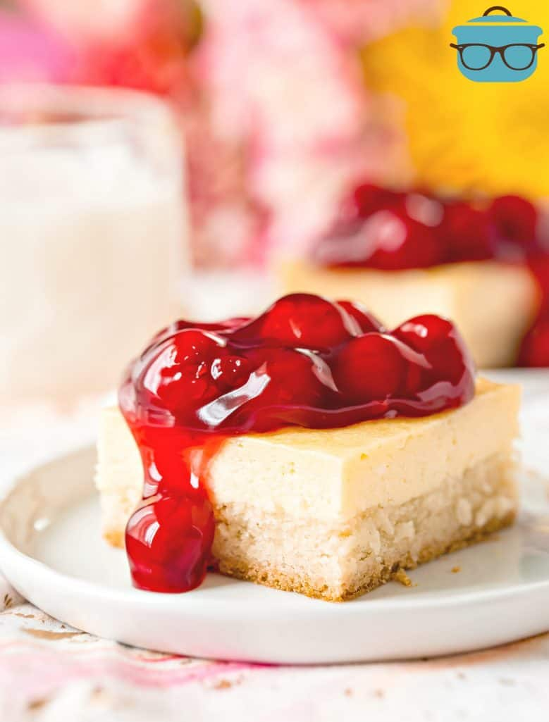 Sugar Cookie Cherry Cheesecake Bar, shown sliced on a white plate with cherry pie filling topping