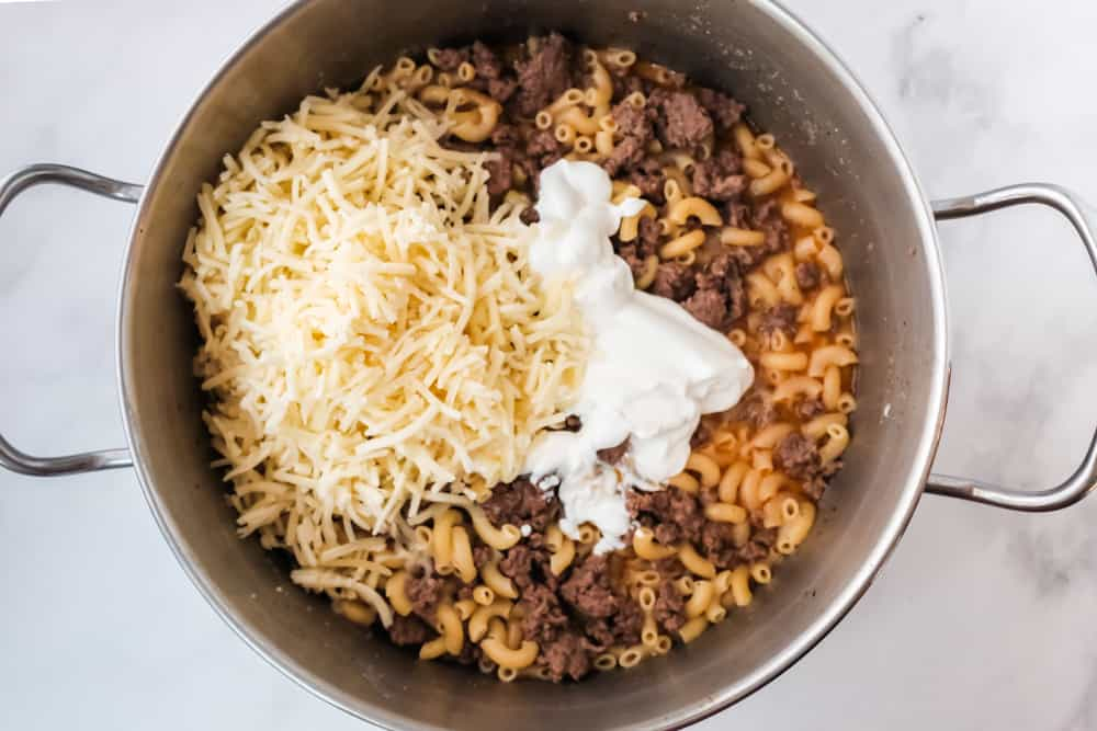 shredded cheddar cheese and sour cream added to macaroni and ground beef mixture in pot