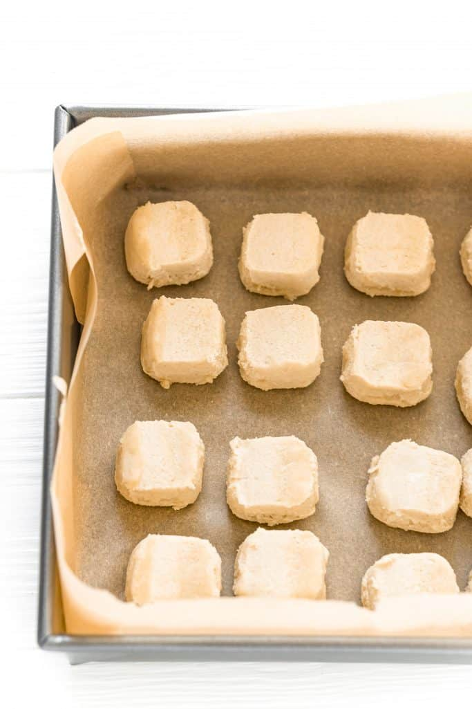 sugar cookie dough placed into the bottom of a parchment lined baking pan