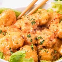 fully cooked Air Fryer Bang Bang Shrimp on a bed of lettuce in a white bowl with chopsticks