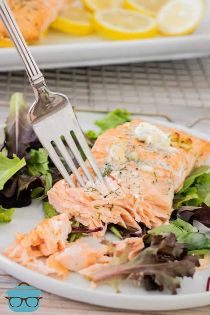 fully cooked salmon on a bed of lettuce with a fork on the salmon slice