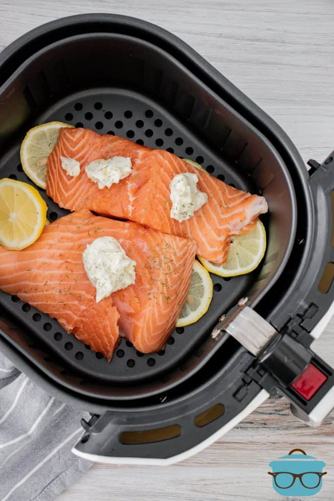 slices of fresh salmon in an air fryer basket with lemon slices and lemon garlic dill butter
