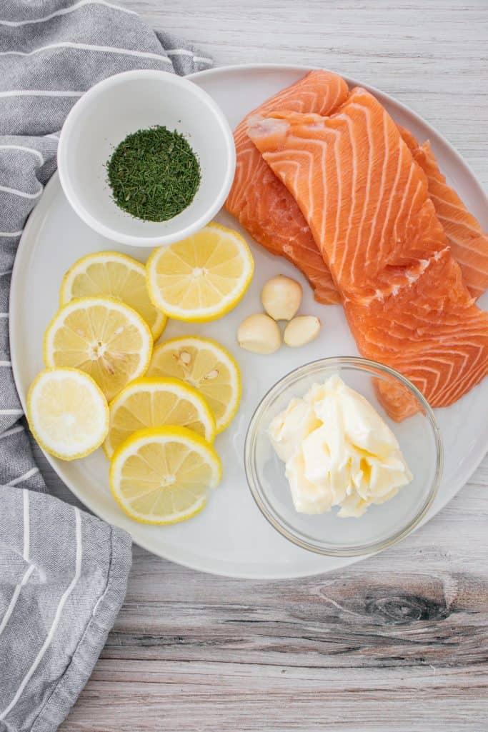 salmon fillets, Salt and pepper, large lemon, sliced, unsalted butter, garlic cloves, lemon juice, freeze dried dill