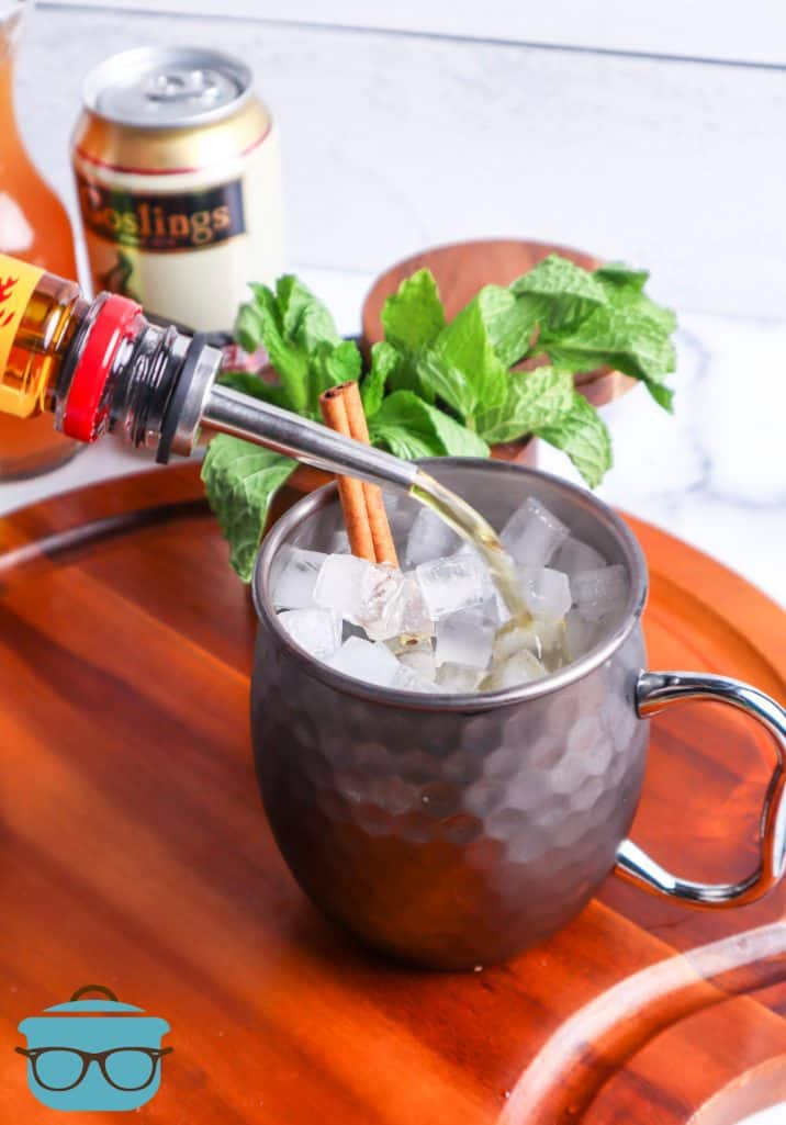Fireball alcohol being poured into a Moscow Mule Mug