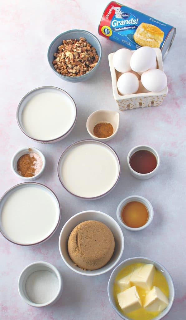 refrigerator biscuits, heavy cream, half and half, milk, eggs, sugar, vanilla extract, apple pie spice, butter, brown sugar, chopped pecans, corn syrup, ground cinnamon