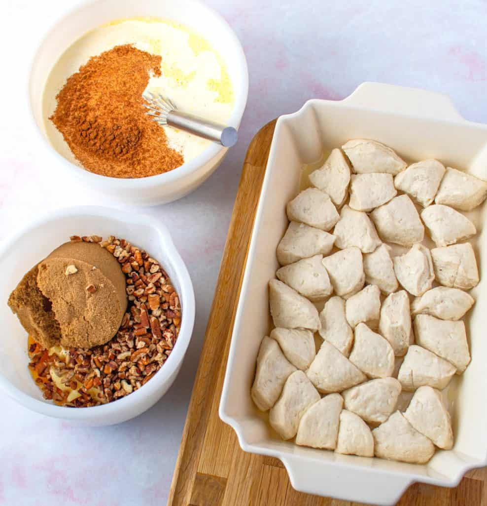refrigerated biscuit pieces placed into the bottom of a cream-colored baking dish