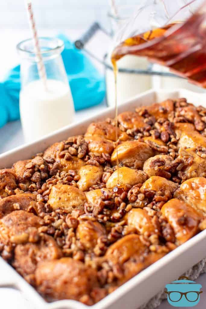pouring maple syrup over fully baked French toast casserole in a cream baking dish