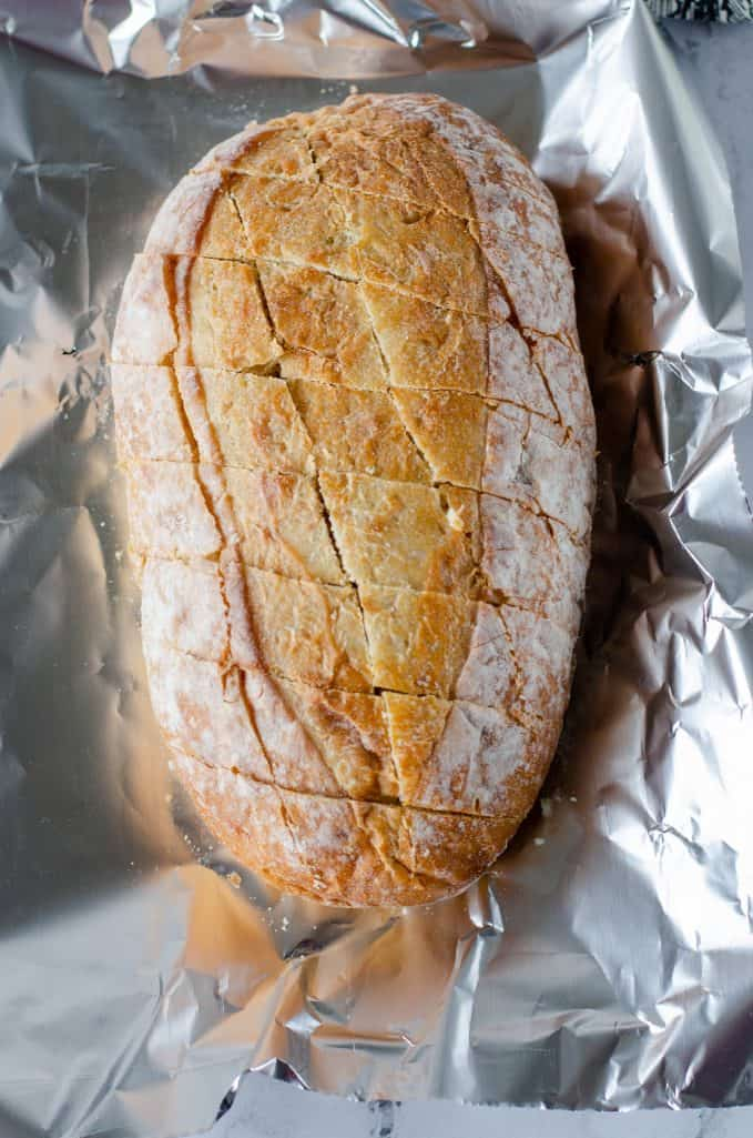 oval ciabatta loaf bread cut diagonally in two directions, bread shown on aluminum foil