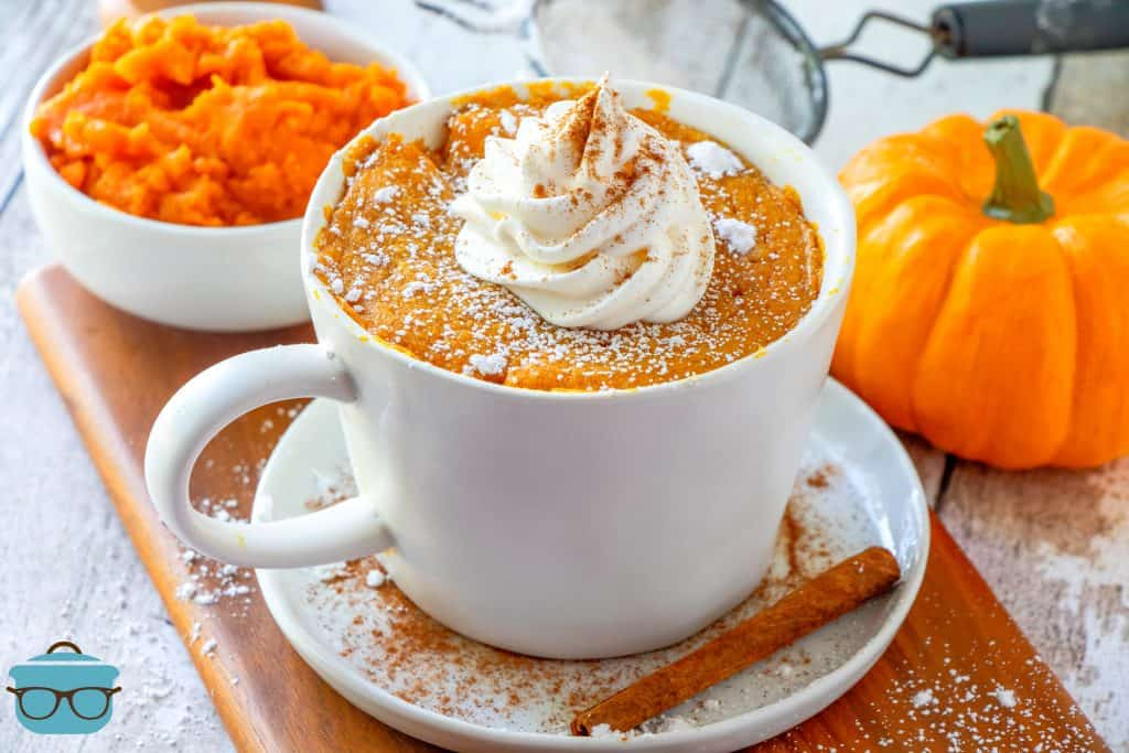 Homemade Pumpkin Mug Cake shown with powdered sugar, background shows a small pumpkin and a bowl of pumpkin puree