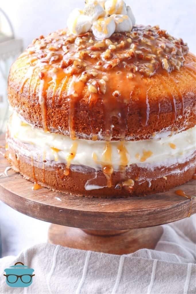Loaded Sweet Potato Layer Cake shown on a wooden pedestal with pecan glaze drizzling down the sides of the cake