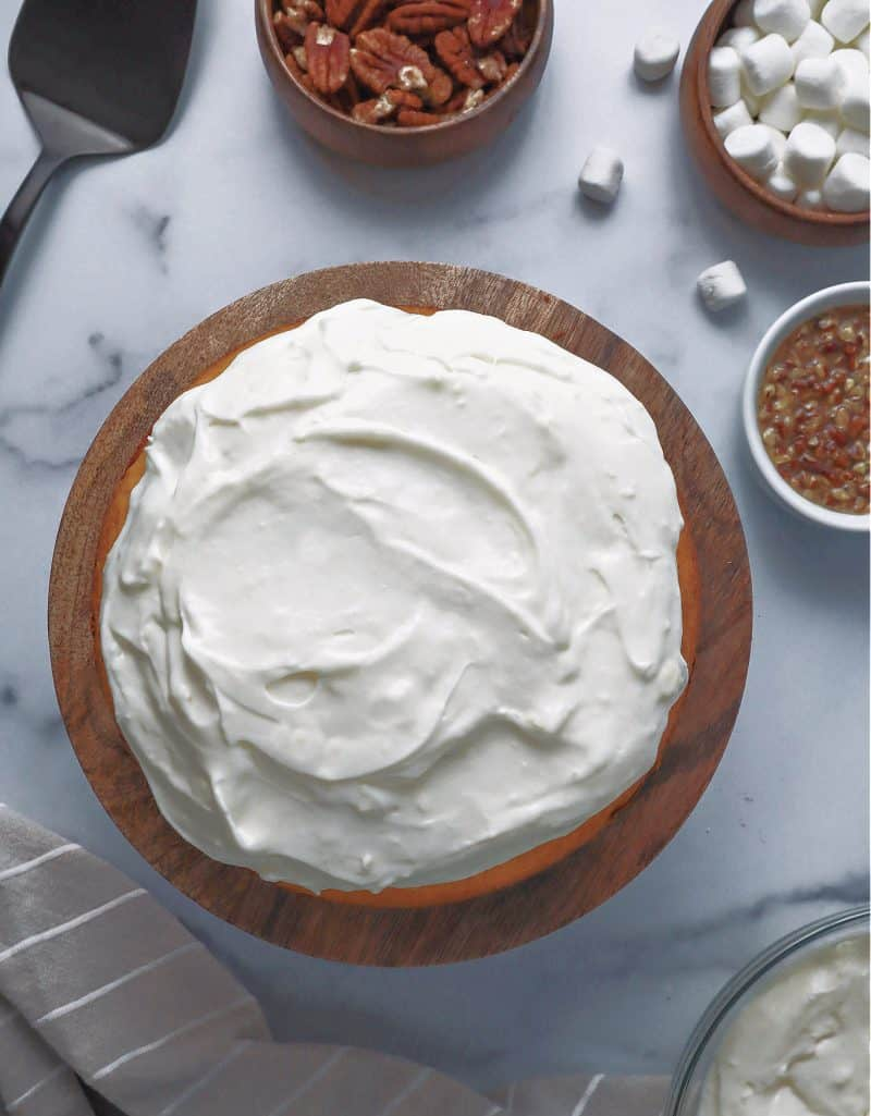 marshmallow frosting spread on top of sweet potato cake layer