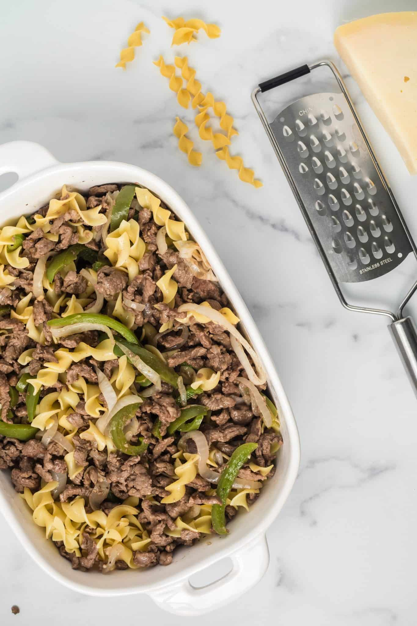 cooked egg noodles, cooked steak, green peppers and onion added to white casserole dish.