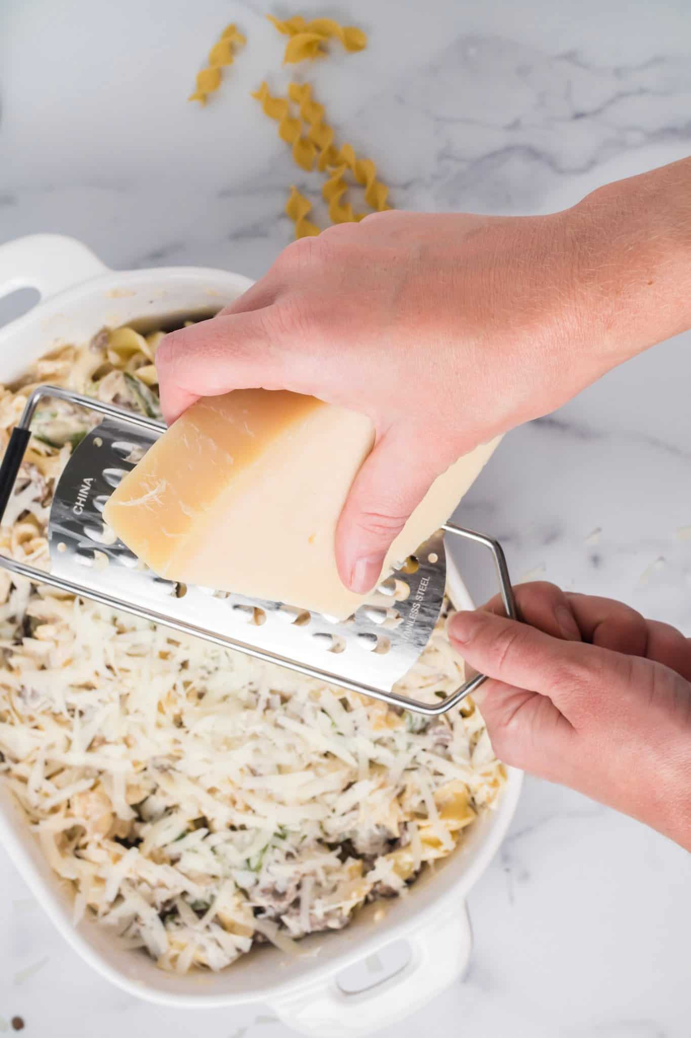 freshly grating provolone cheese on top of Philly cheesesteak casserole.